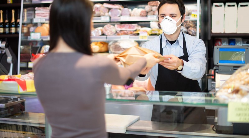 shopkeeper-serving-a-customer-while-wearing-a-mask-min-scaled